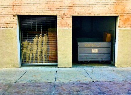 dumpster and mannequins in alley